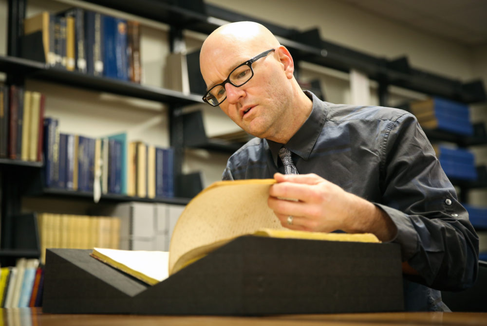 Phillip Troutman is shown poring over a large book at GW's Gelman Library.