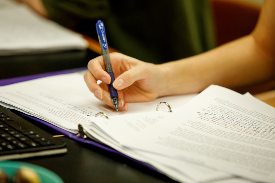 A person's hand holding a pen over a notebook