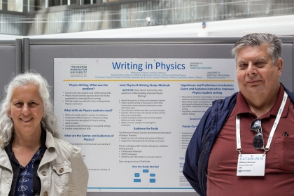 """Prof. Rachel Riedner (left) and prof. Bill Briscoe (right) in front of the """"writing in physics"""" poster"""